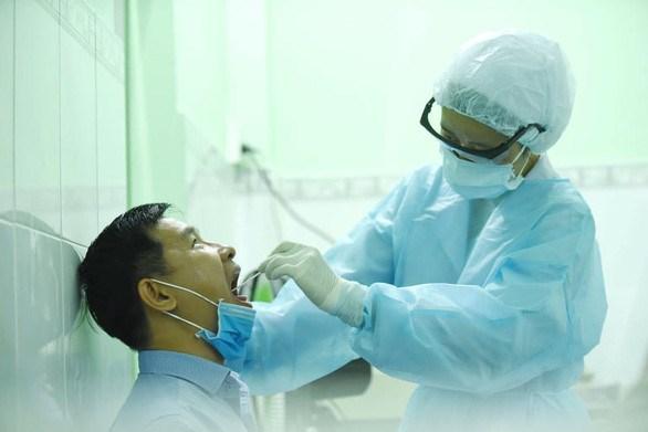 Nhân viên y tế lấy dịch phết họng một người dân TPHCM từ Đà Nẵng trở về tại trạm y tế P.17, Q.Bình Thạnh. Ảnh: Duyên Phan/báo Tuổi Trẻ.